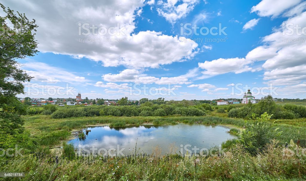 Suzdal landscape with pond reflections of curly clouds and blue sky stock photo