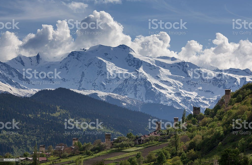 Svan watchtowers  the background of snow-capped mountain peaks  clouds stock photo