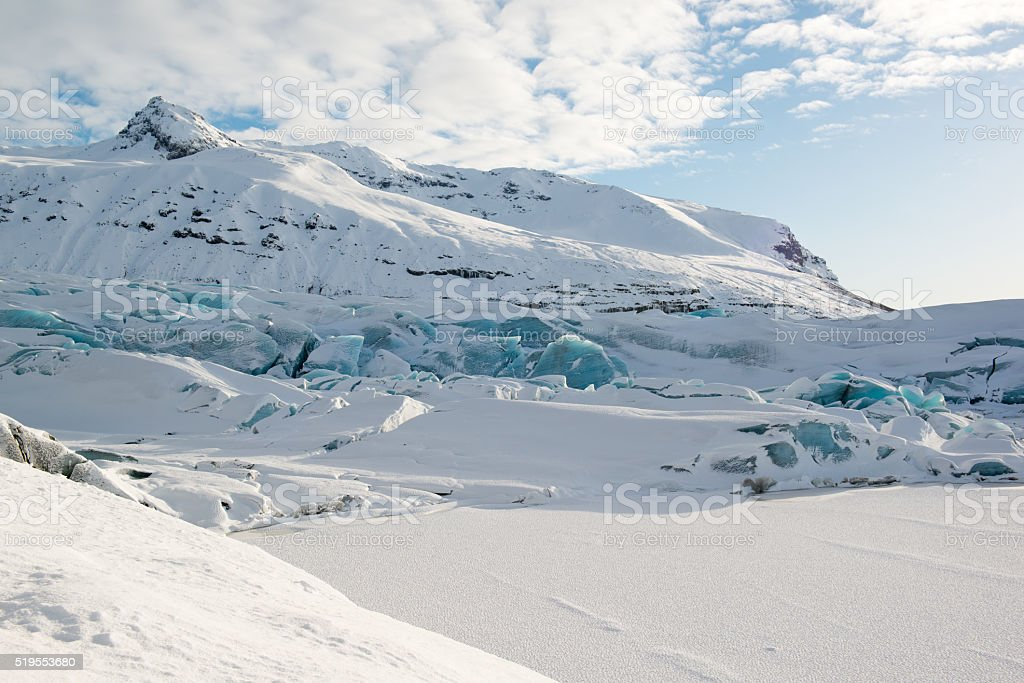 Svinafellsjokull glacier tongue, winter, blue icebergs covered by snow, Iceland stock photo