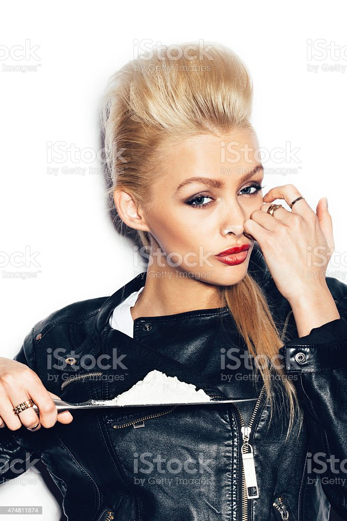 Swag girl in black leather jacket sniffing cocaine stock photo