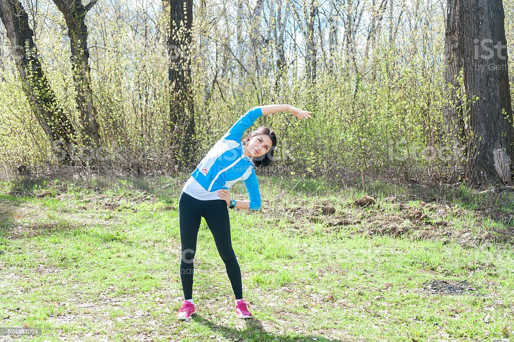 Swarthy young girl doing gymnastic exercises outdoors stock photo