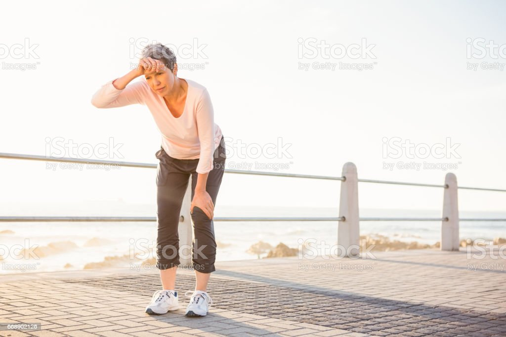Sweating sporty woman resting at promenade stock photo