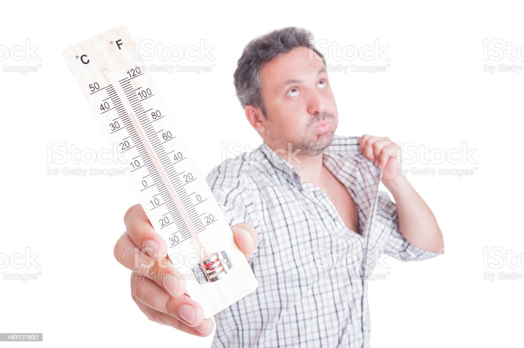 Sweaty man holding thermometer as summer heat concept stock photo