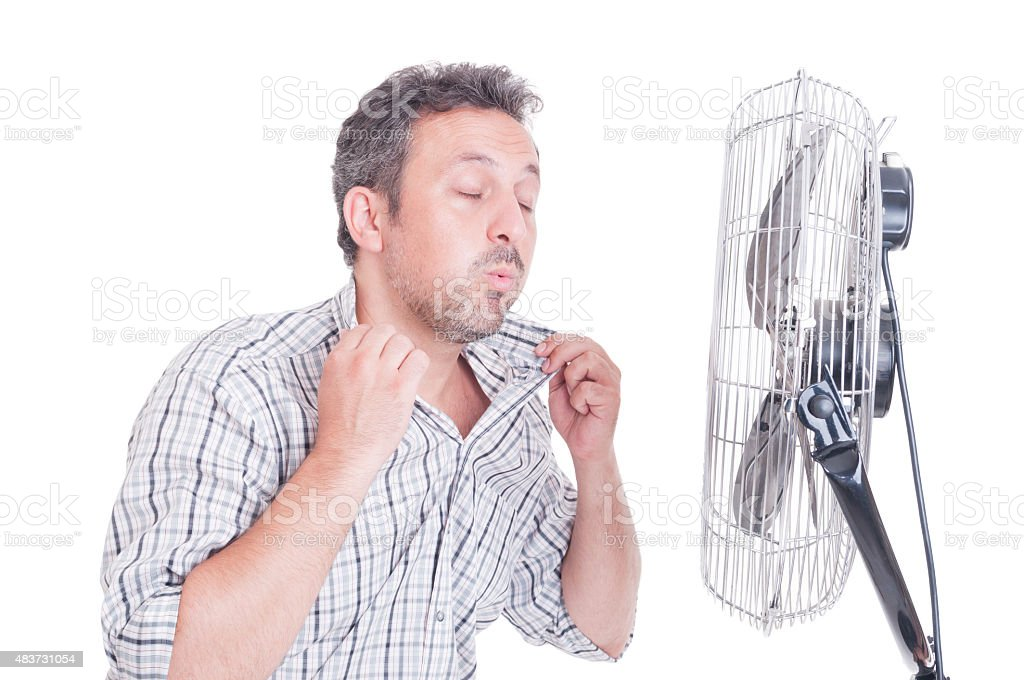 Sweaty man opening shirt in front of cooling fan stock photo