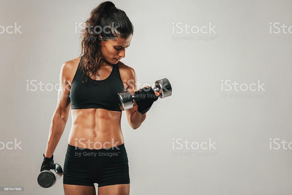 Sweaty woman curling dumbbell stock photo