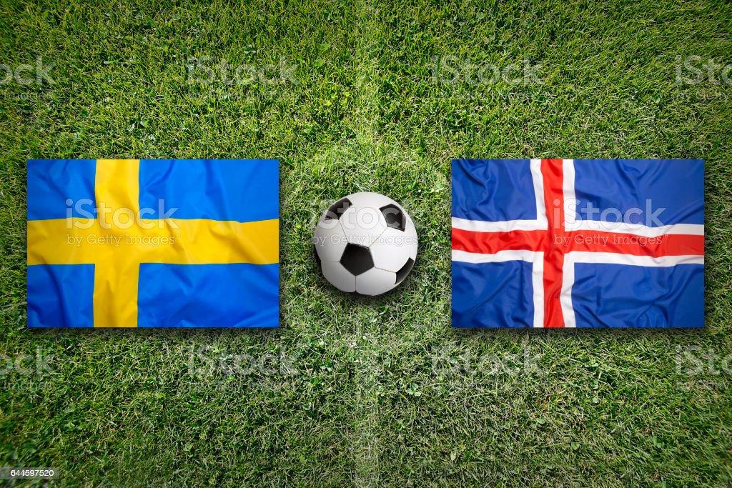Sweden vs. Iceland flags on soccer field stock photo