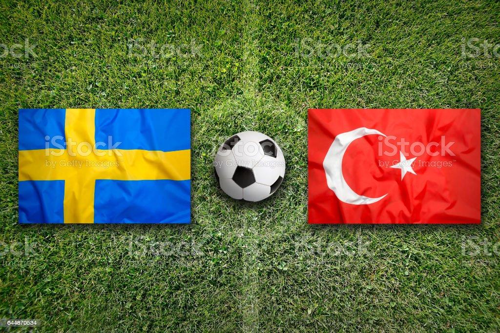 Sweden vs. Turkey flags on soccer field stock photo