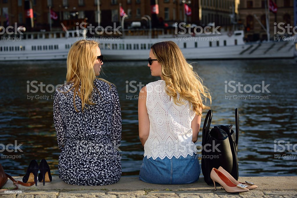 Swedish blonde women in Stockholm, Strandvagen, Nybrokajen, shoes off stock photo
