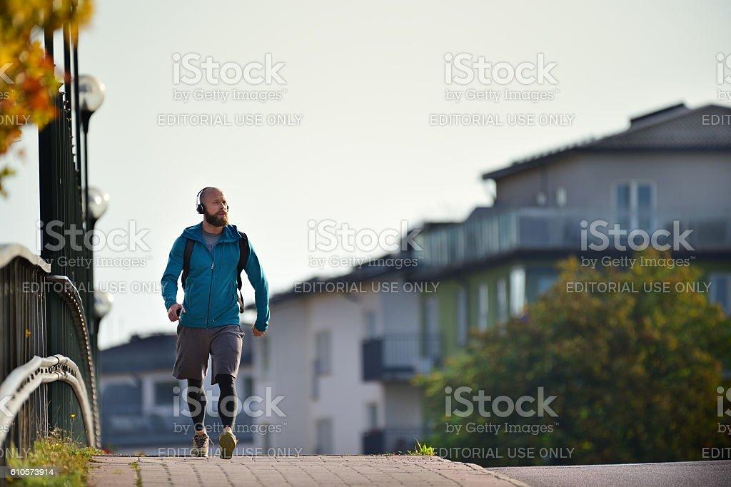 Swedish man, using mobile smart phone, walking on sidewalk stock photo