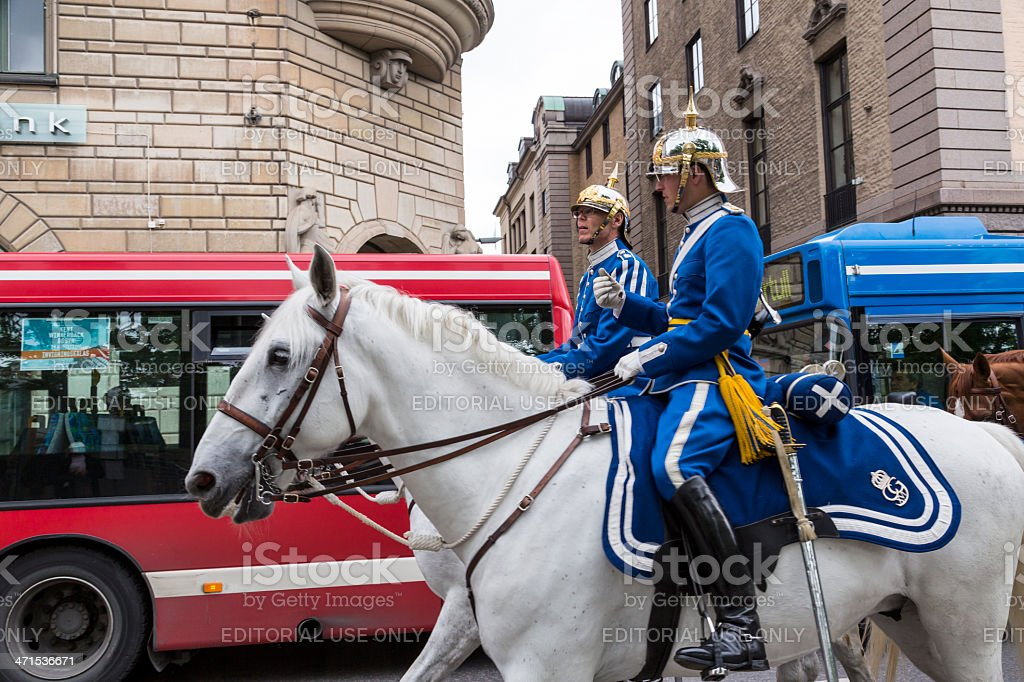 Swedish Mounted Guard passing a blue bus in Stockholm royalty-free stock photo