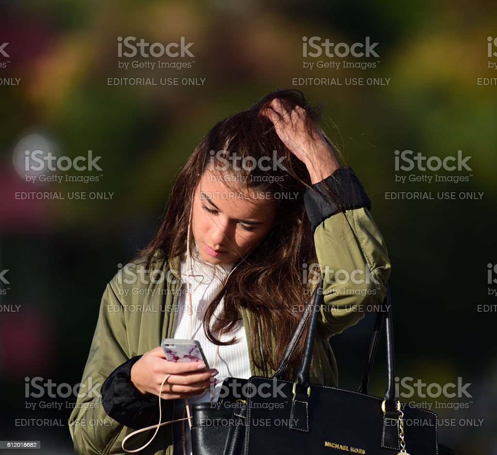 Swedish young woman, phone and headphones stock photo