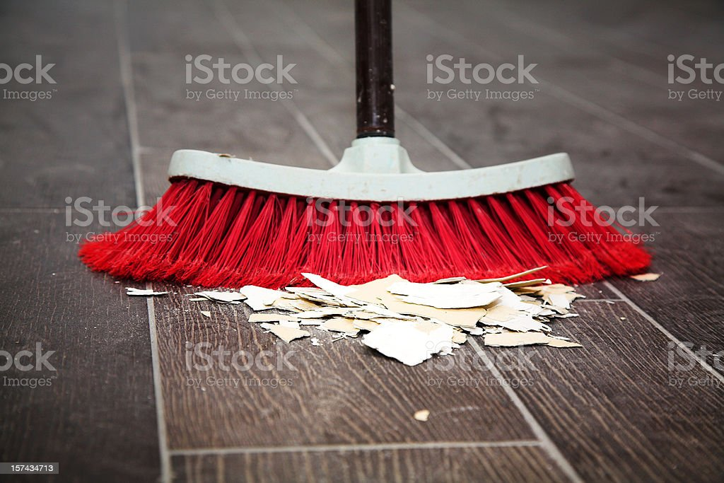 Sweeping the wooden floor with a broom stock photo