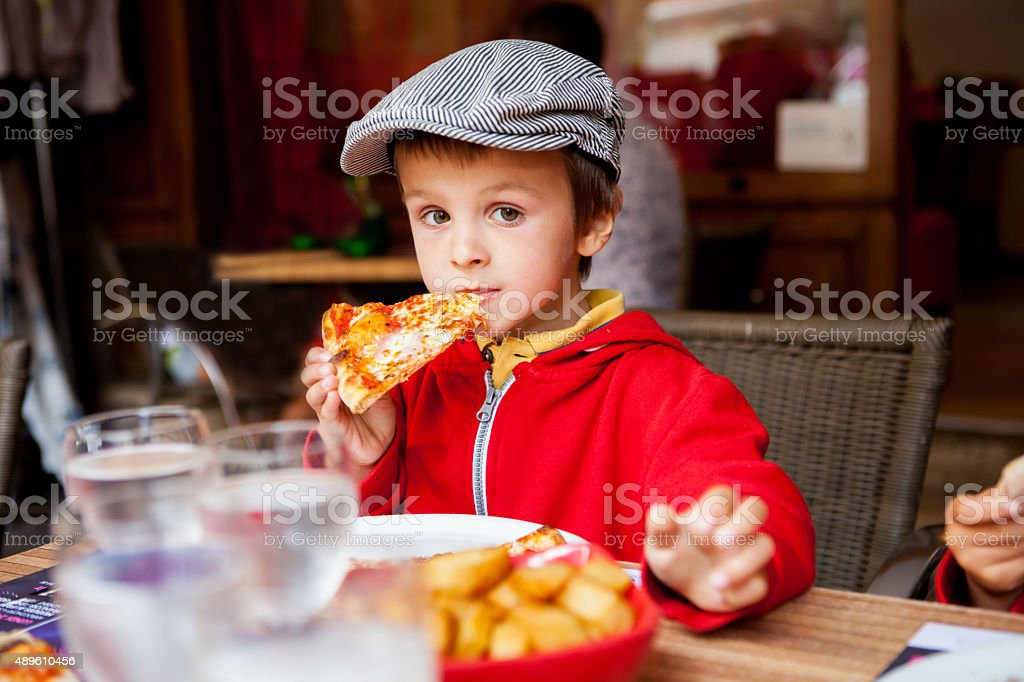 Sweet adorable child, boy, eating pizza at a restaurant stock photo