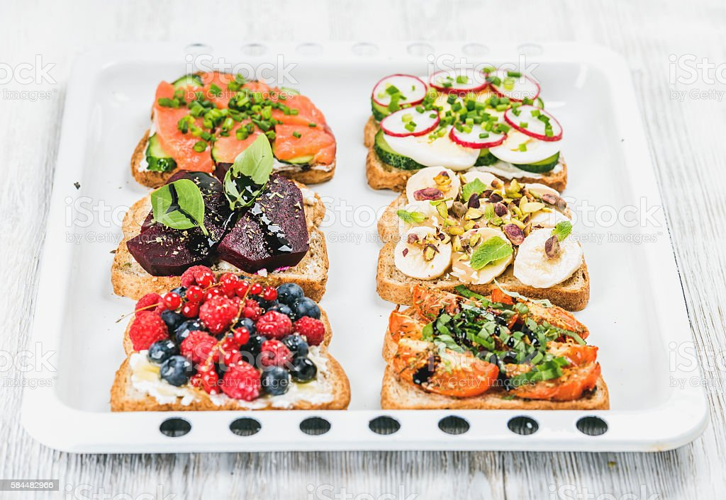 Sweet and savory breakfast toasts variety. Sandwiches with fruit, vegetables stock photo