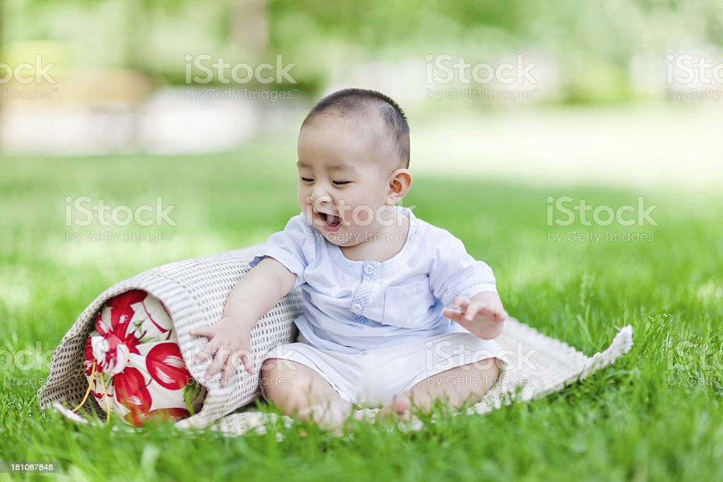 Sweet Asian little baby boy sitting on lawn royalty-free stock photo