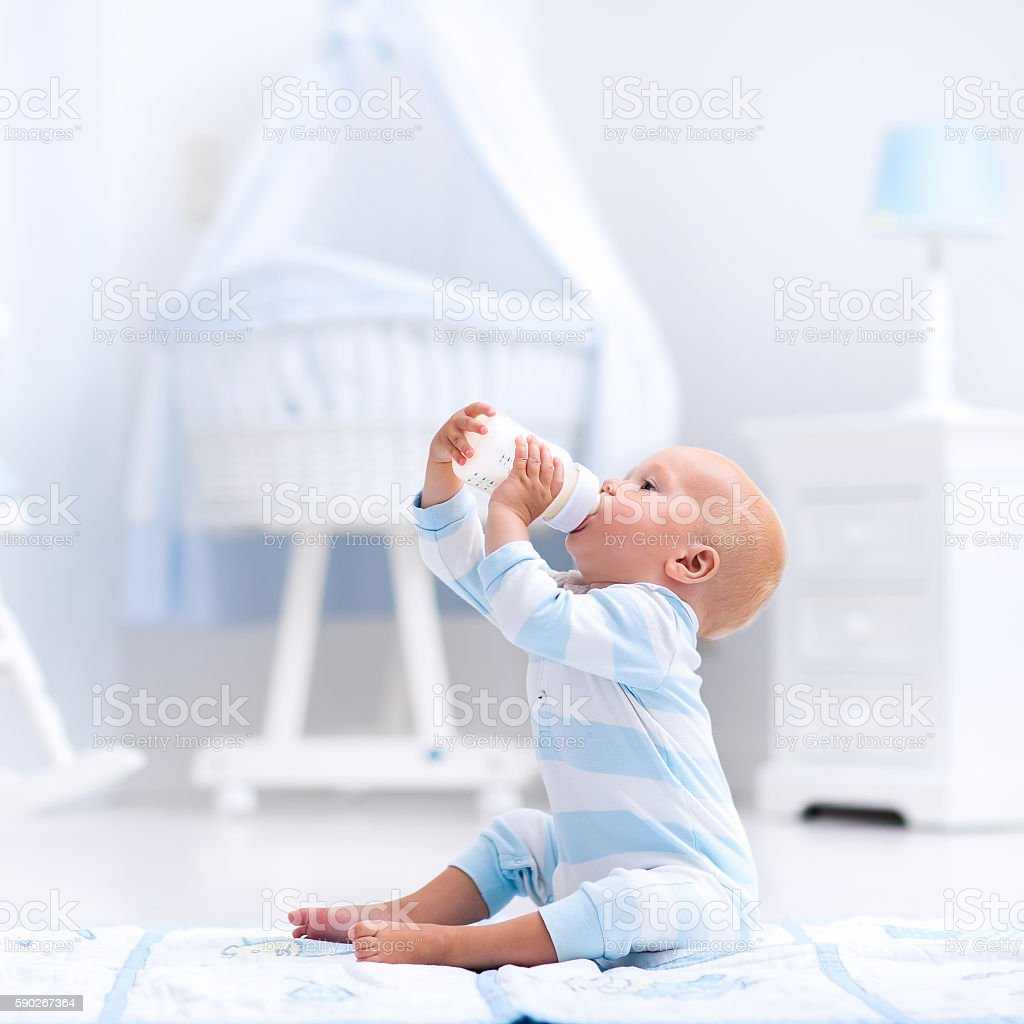 Sweet baby boy drinking milk in sunny nursery stock photo