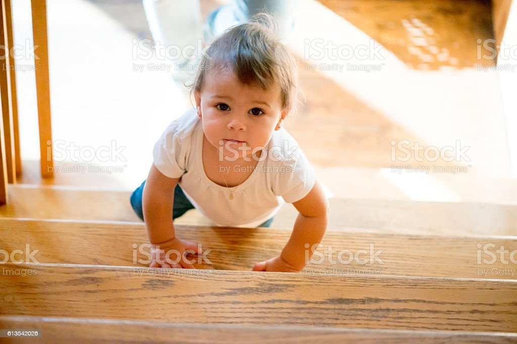 Sweet baby girl is walking up the stairs stock photo