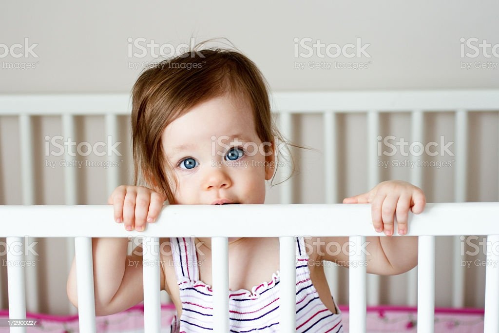 Sweet baby girl looking out over her crib rail stock photo