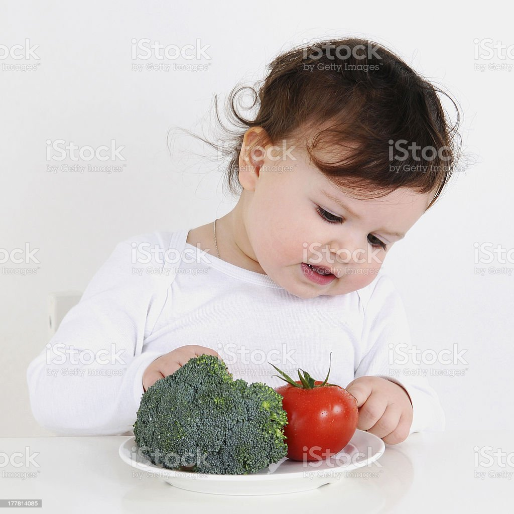 Sweet baby girl looking to wegetables royalty-free stock photo