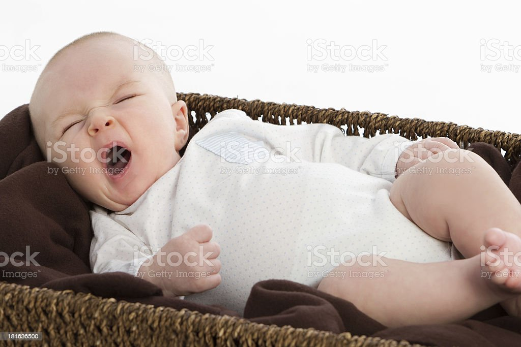 Sweet baby yawning in a basket royalty-free stock photo