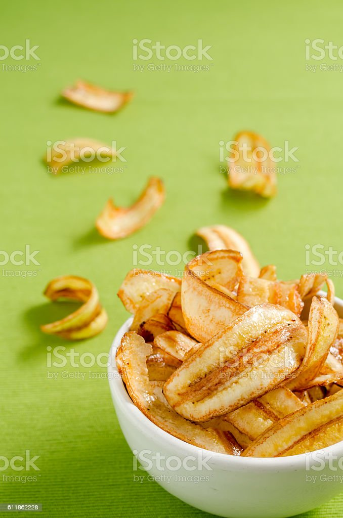 Sweet banana chips on green tablecloth background stock photo