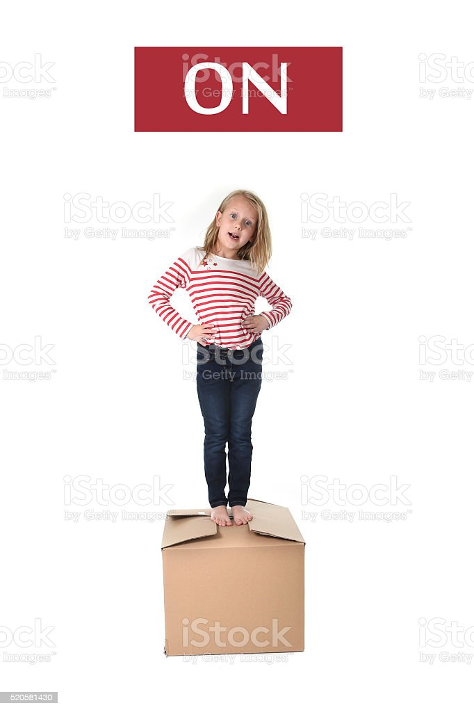 sweet blond child and cardboard box learning english prepositions stock photo