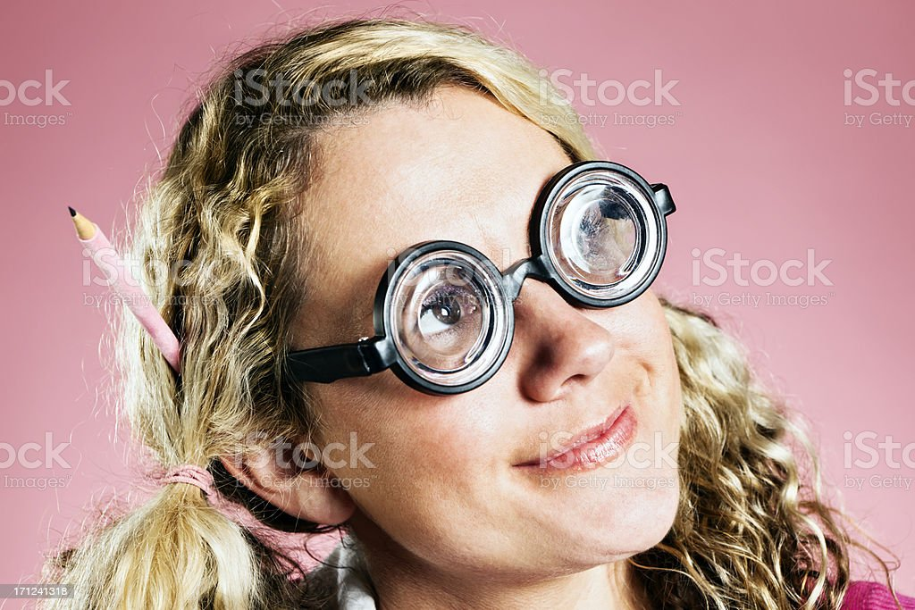 Sweet blonde geek with pen in hair smiles dreamily royalty-free stock photo