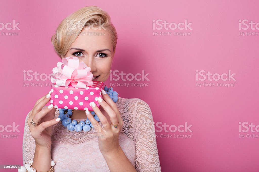 Sweet blonde woman holding small gift box with ribbon. Soft stock photo