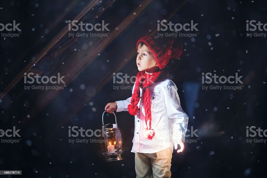 Sweet boy, holding a lantern, looking at light coming through stock photo