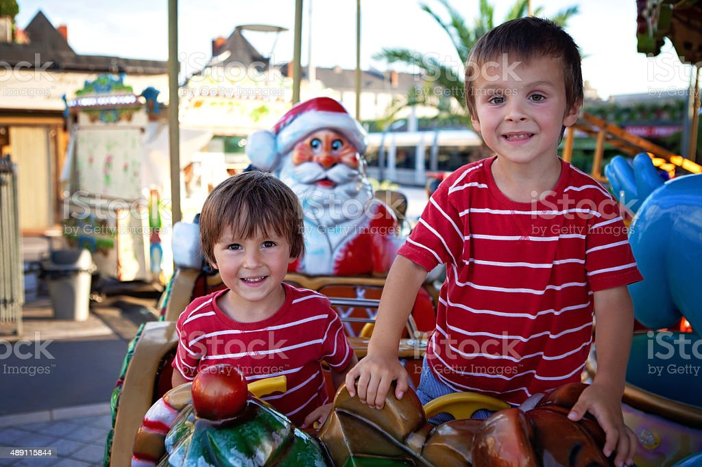 Sweet boys, brothers, riding in Santa Claus sledge on carousel stock photo