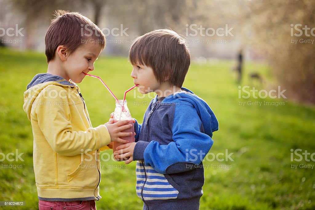 Sweet boys in the park, holding bottle with smoothie, drinking stock photo