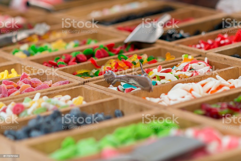sweet candies on a market in wooden boxes stock photo