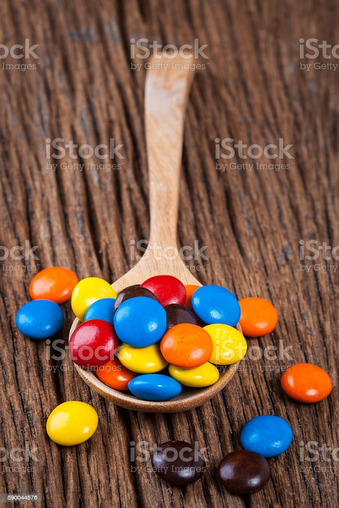 sweet candy chocolate in spoon on wood table stock photo