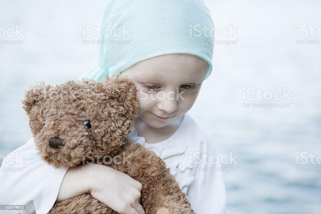 Sweet Chemo Girl Hugs Teddy Bear stock photo