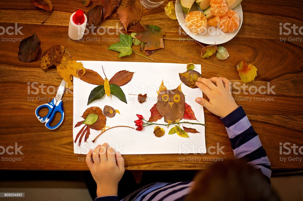 Sweet child, boy, applying leaves using glue while doing arts stock photo