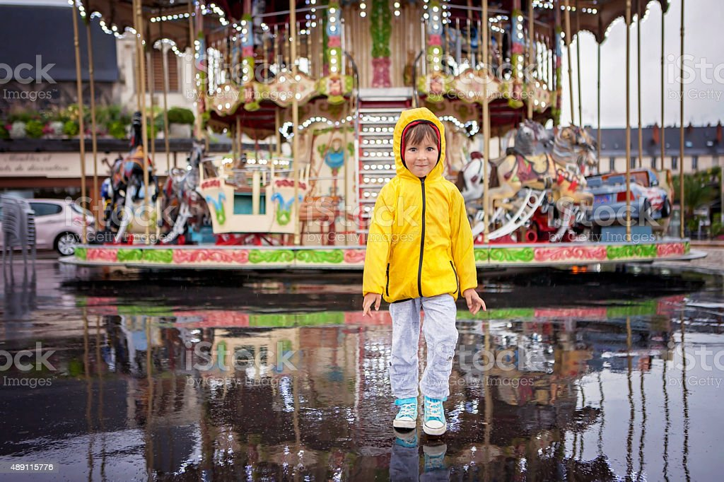 Sweet child, boy watching carousel in the rain stock photo