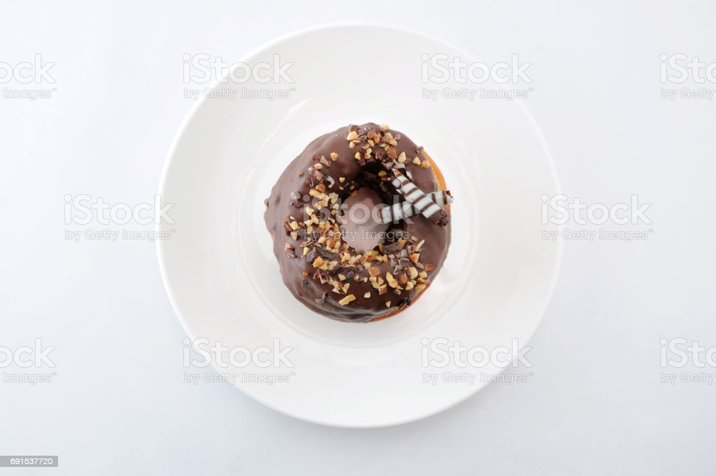 sweet chocolate almond cake doughnut on a plate white background stock photo