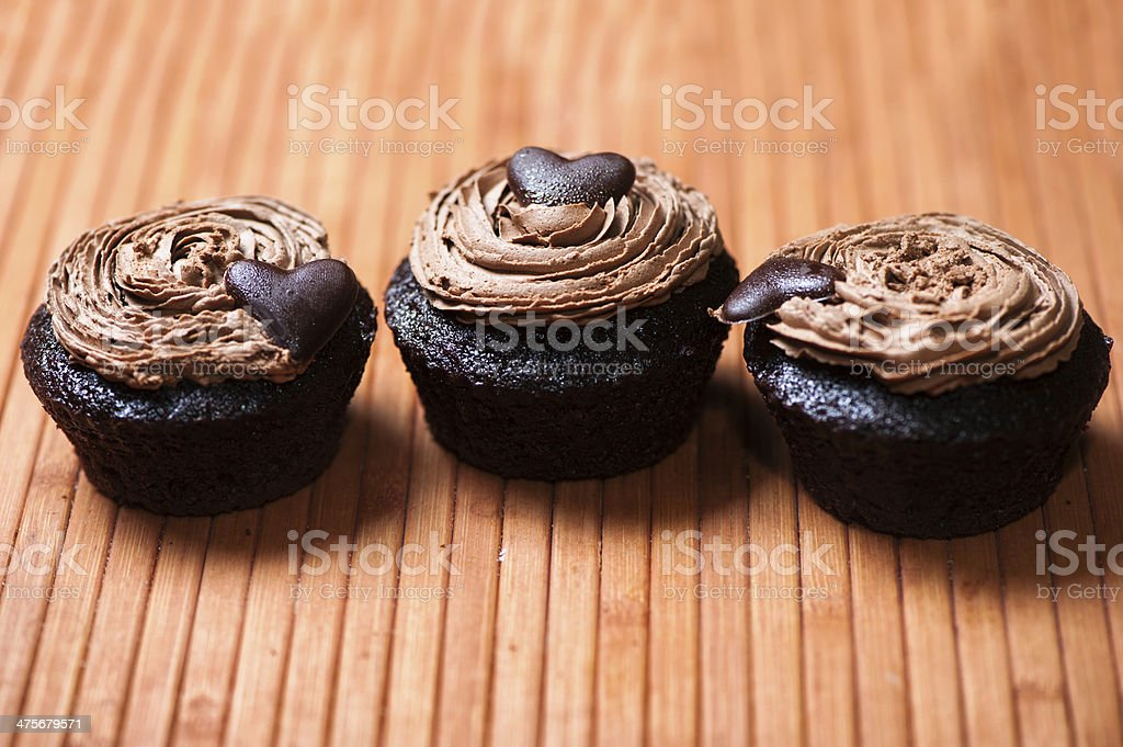 Sweet chocolate creamy muffins with heart as a cookie stock photo