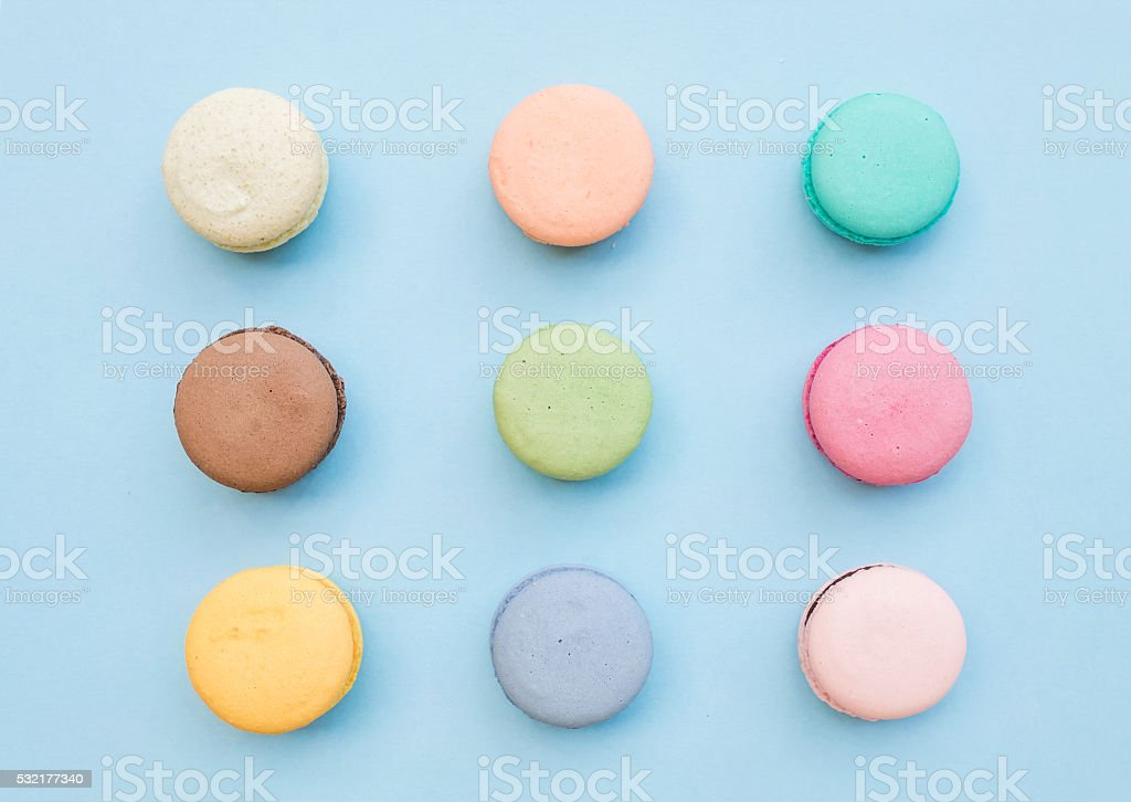 Sweet colorful French macaroon biscuits on pastel blue background stock photo