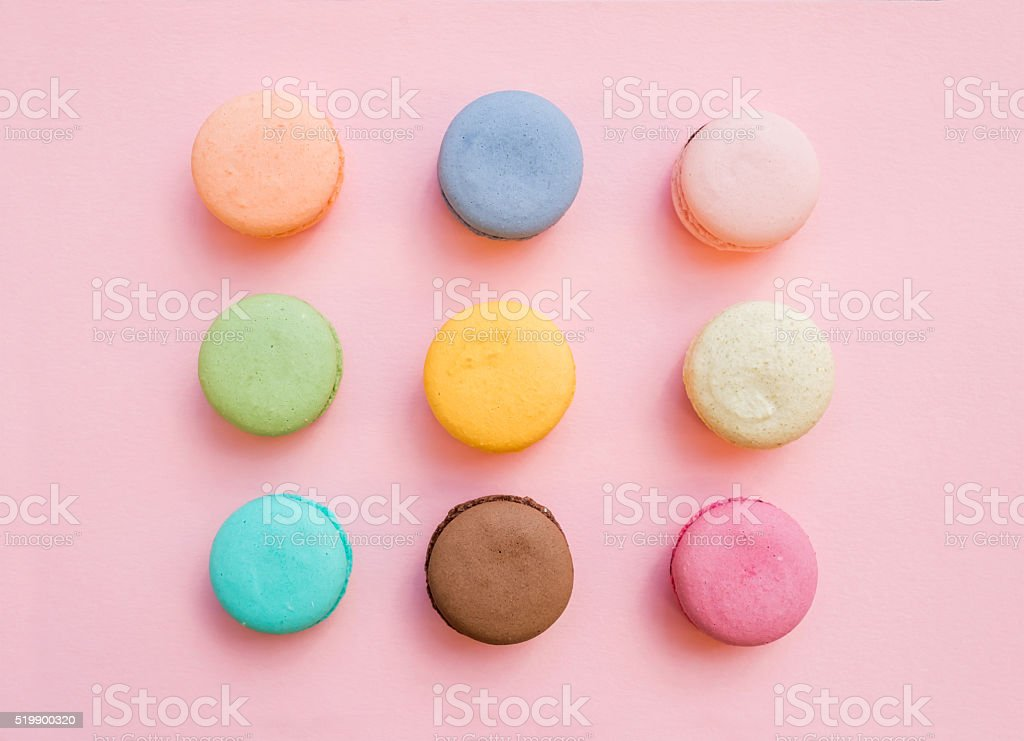 Sweet colorful French macaroon biscuits on pastel pink background stock photo