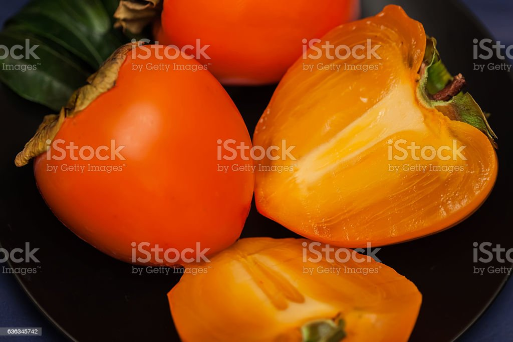 Sweet, delicious cut a ripe Persimmon in black plate, low stock photo