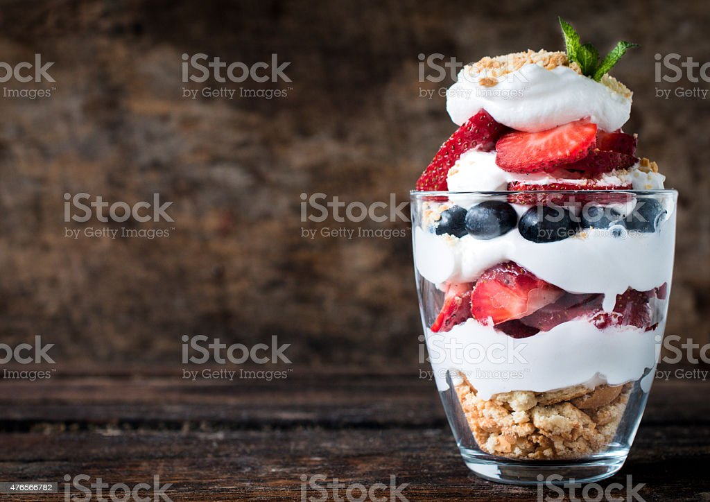 Sweet dessert in glass with biscuit,berry fruit and whipped...