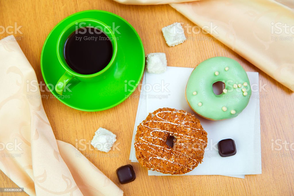 Sweet donuts and cup of black coffee stock photo