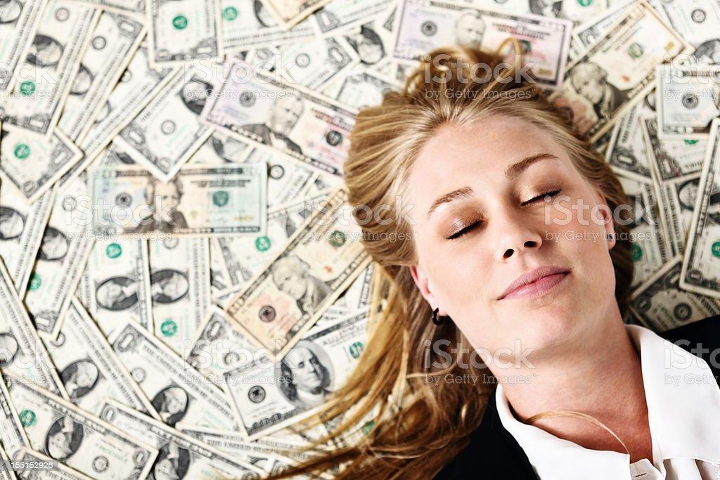 Sweet dreams as beautiful blonde sleeps on pile of dollars stock photo
