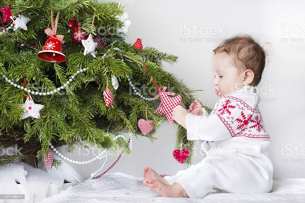 Sweet funny baby girl playing with Christmas tree decoration royalty-free stock photo