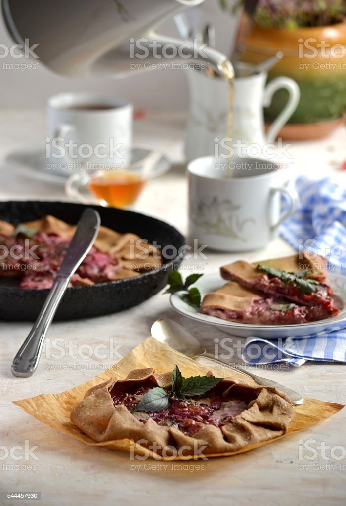 sweet Galette with plums and basil on a white table stock photo