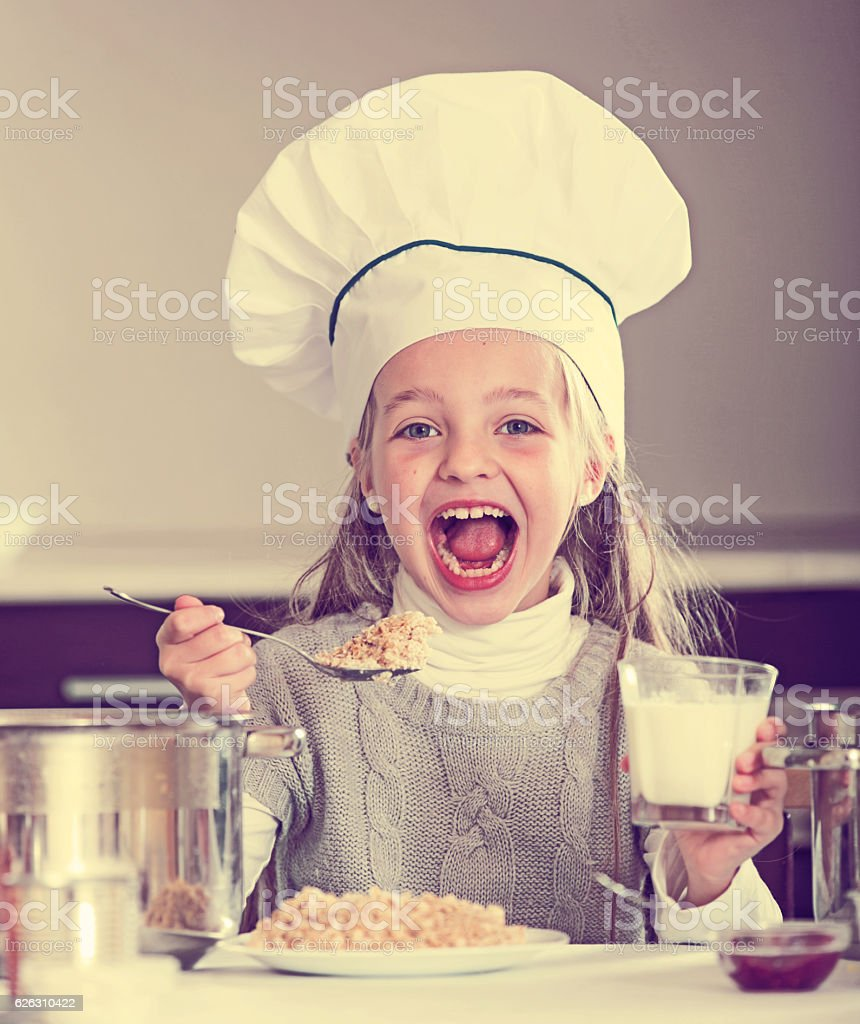 Sweet girl in cook hat eating kasha in kitchen stock photo