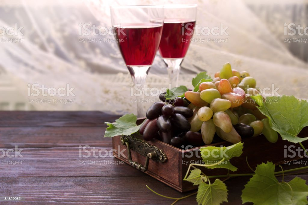 Sweet grape branches and two wine glasses, ripe fruits with green leaves  in wooden box stock photo