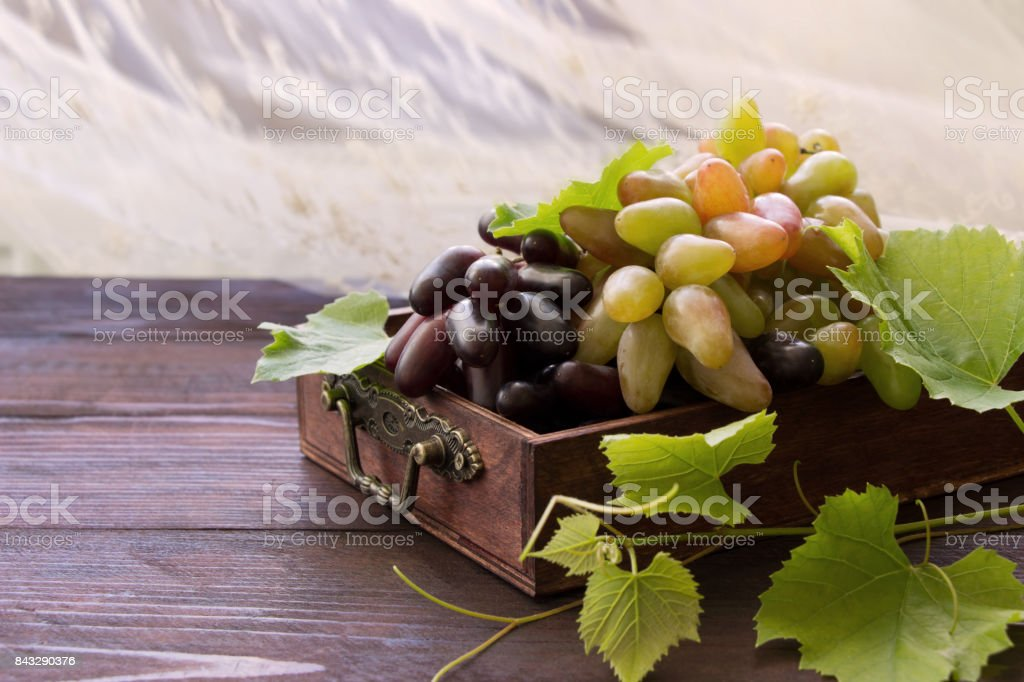 Sweet grape branches , ripe fruits with green leaves  in wooden box ,grape harvest stock photo