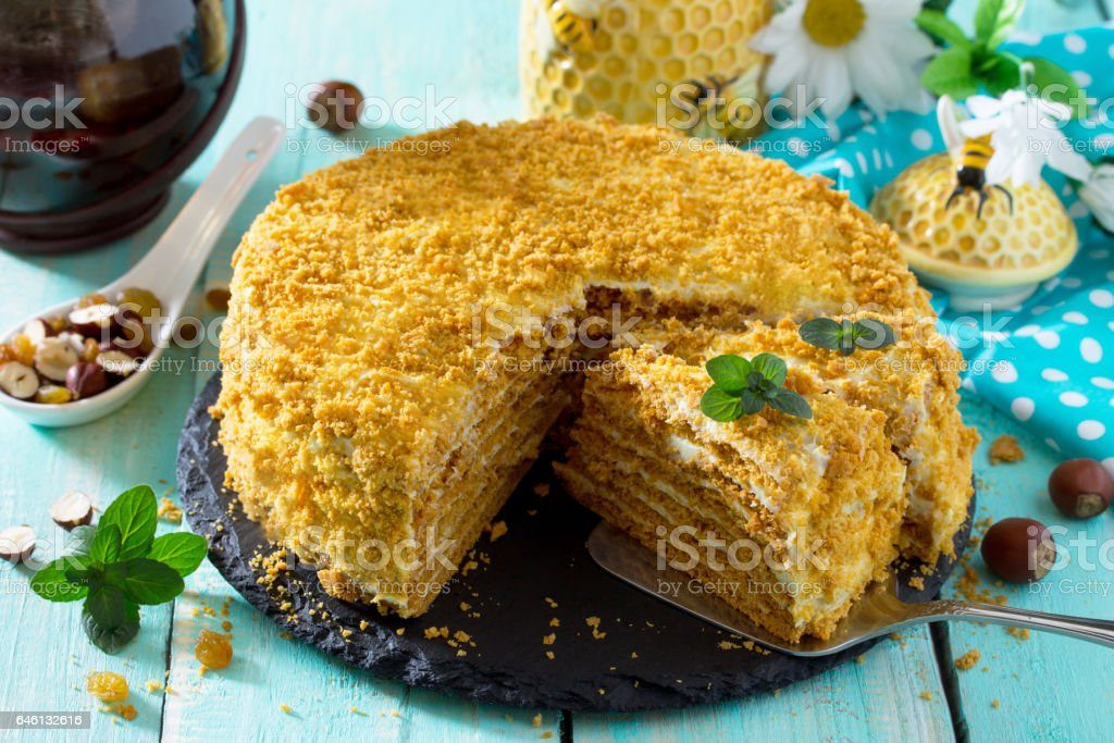 Sweet home layered honey cake on a wooden table with raisins and nuts. stock photo